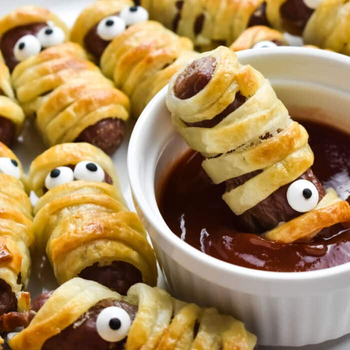 Halloween Sausage Mummies on a plate with one dipped in tomato sauce