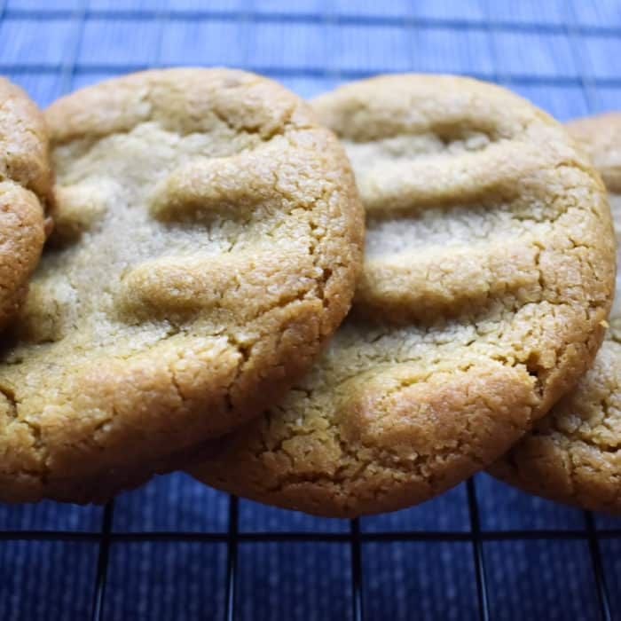peanut butter cookies on a wire rack on a blue tea towel