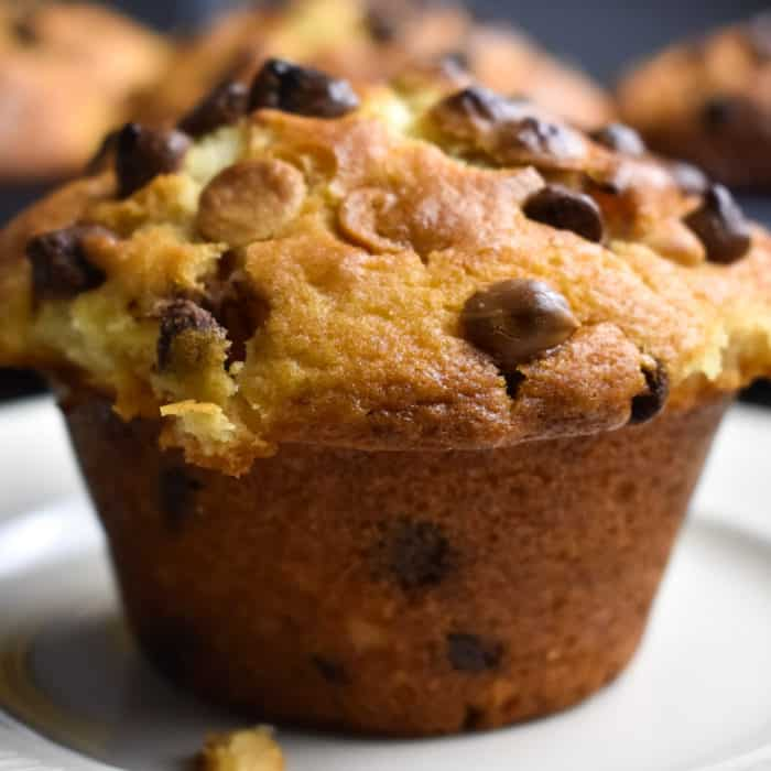 Chocolate Chip Muffin on a beige plate with muffins at the back
