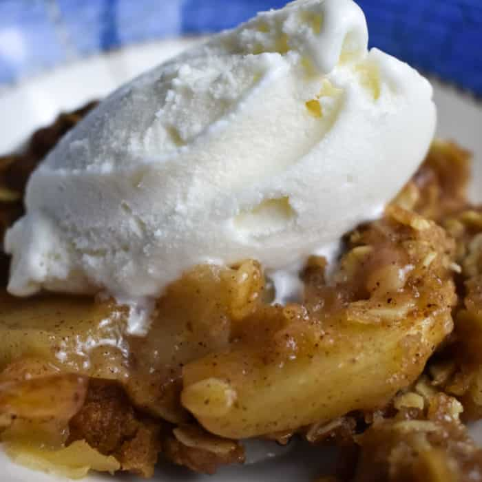Apple Crumble in a white and blue bowl with ice cream on top
