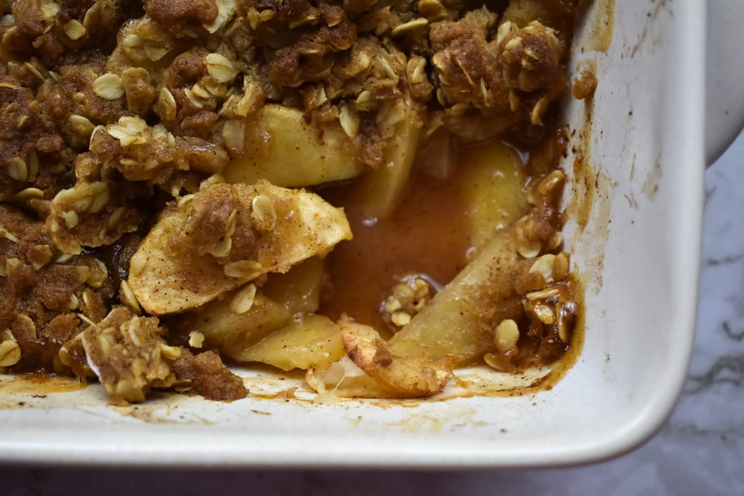 Apple crumble in a baking dish on a marble surface